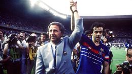 France coach Michael Hidalgo holds aloft captain Michel Platini's arm after the final of the 1984 European Championship