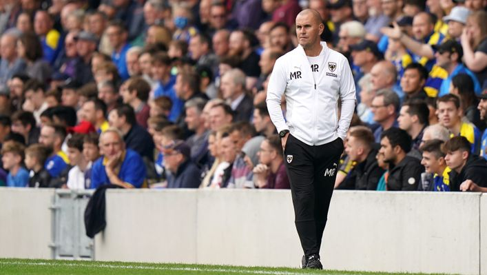 Mark Robinson will eye a famous upset as AFC Wimbledon travel to Arsenal