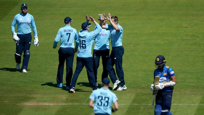 Chris Woakes' team-mates celebrate with him after taking one of his four wickets against Sri Lanka