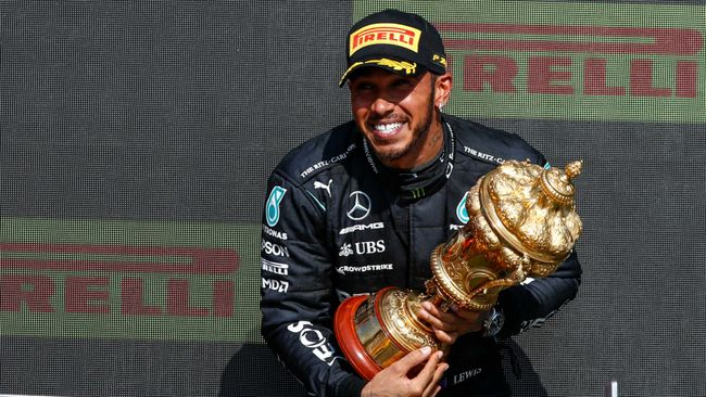 Lewis Hamilton hugging the British Grand Prix trophy after  his controversial win at Silverstone